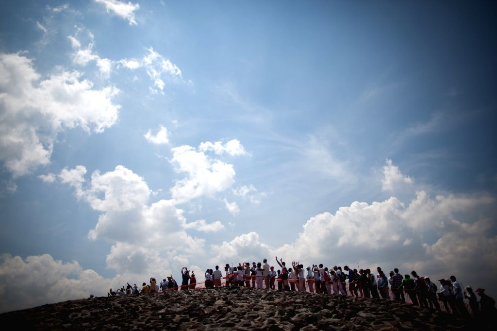 Visitors raise their arms during the celebration of the spring equinox in the archaeological site of Teotihuacan, State of Mexico, Mexico on March 21, 2015. ...