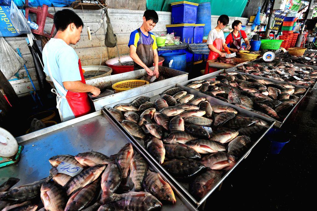 Thai market workers sell fresh fish at a market in Bangkok, Thailand, Oct. 30, 2015.