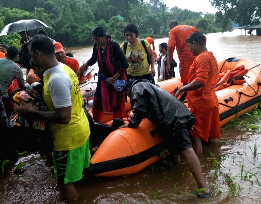 Thane: Passengers stranded in the Mahalaxmi Express on the flooded railway tracks at Vangani being rescued, in Maharashtra's Thane on July 27, 2019. The Indian Air Force (IAF), Navy, Army and the National Disaster Response Force (NDRF) launched a mas