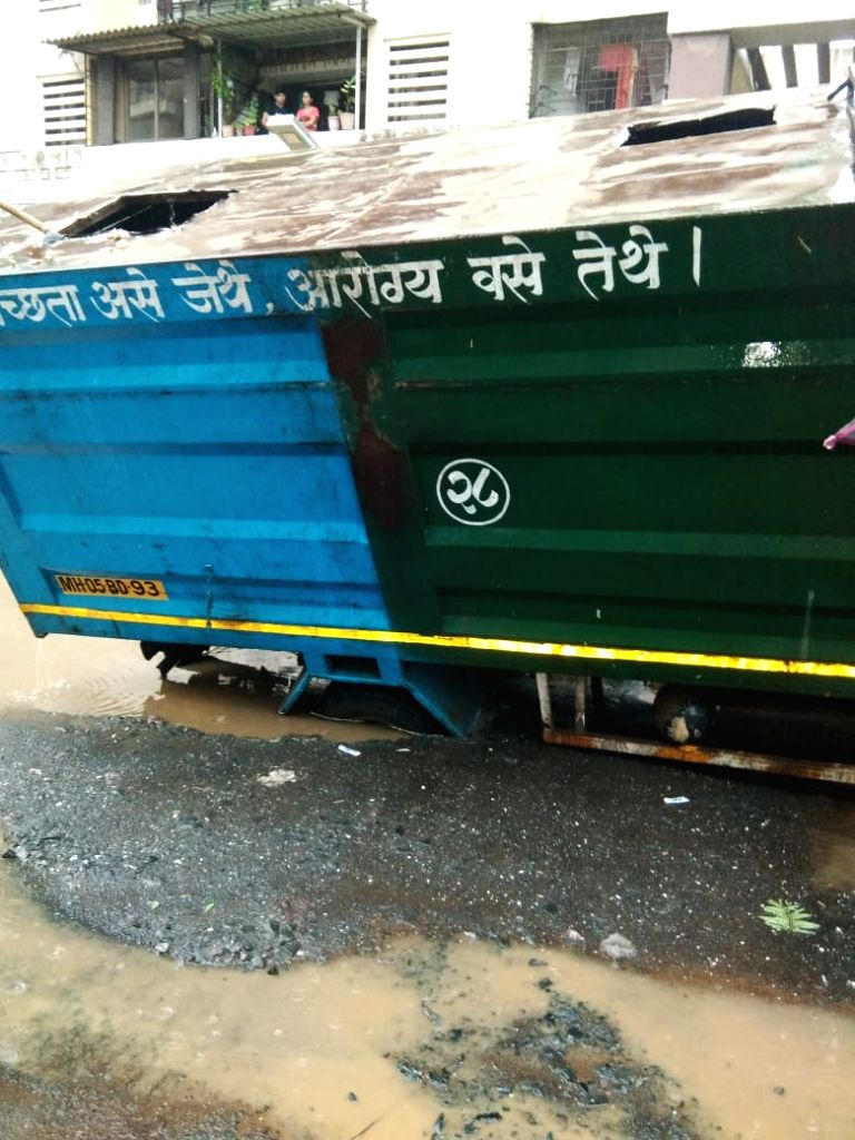 Thane: The tire of a truck got stuck in a pothole after heavy rains lashed Maharashtra's Thane on June 28, 2019. (Photo: IANS)