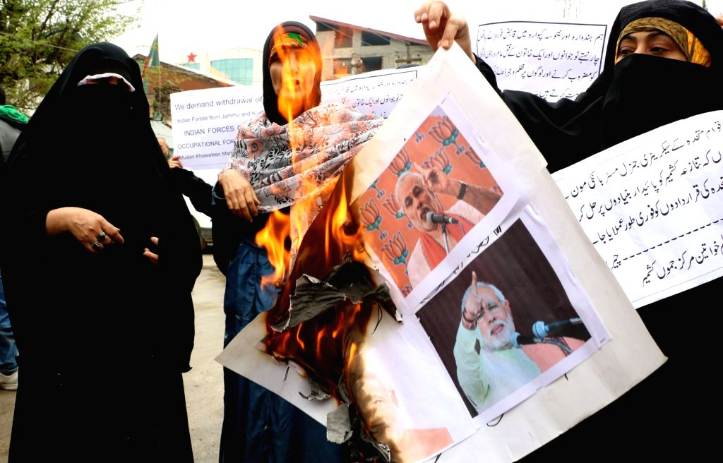 The activists of Muslim Khawateen Markaz Jammu Kashmir burn pictures of Prime Minister Narendra Modi during a protest against civilian deaths in Handwara and Kupwara of the state; in ... - Narendra Modi