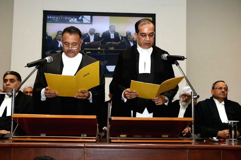 The Chief justice of Punjab & Haryana High Court, Justice Ravi Shanker Jha administers the oath of office to Justice Girish Agnihotri as Punjab and Haryana High Court judge, in ...
