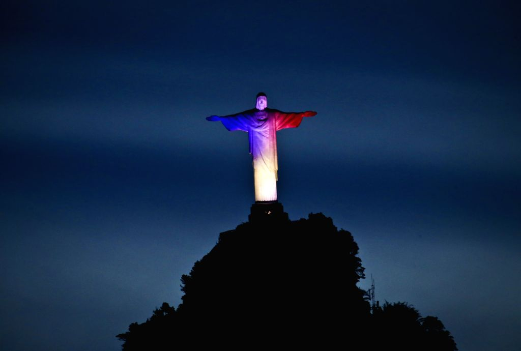The Christ the Redeemer statue is illuminated with the colors of the French national flag to mourn for the victims of the terrorist attacks in Paris, in Rio ...