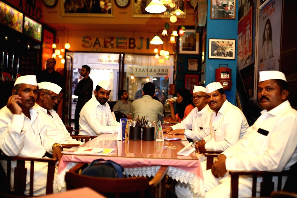 The Dabbawalas and bloggers enjoying the meals served in dabbas at restaurant chain SodaBottleOpenerWala's outlet.
