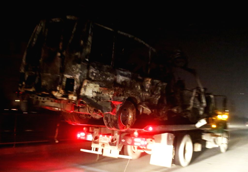 The destroyed vehicle is carried away from the site of a suicide attack in Kabul, capital of Afghanistan, Jan. 20, 2016. At least seven people were killed and 25 ...