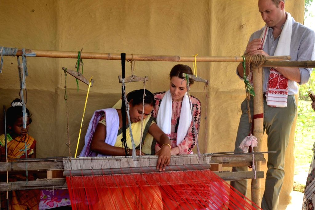 The Duke and Duchess of Cambridge, Prince William and Kate Middleton look at a lady weaving a cloth during their visit to Panbarai Model village near Kaziranga of Assam on April 13, 2016.