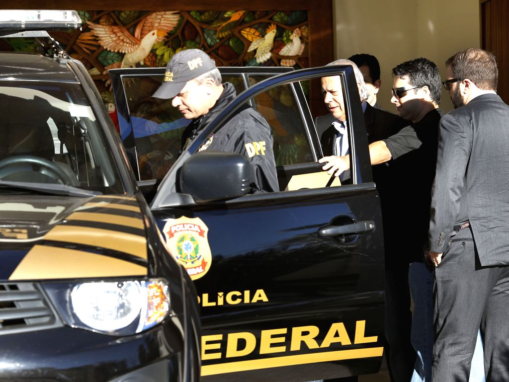 The former Minister Chief of Cabinet of Brazil, Jose Dirceu (C), is escorted to a patrol car after his arrest, in Brasilia, Brazil, on Aug. 3, 2015. The former ... - Chief