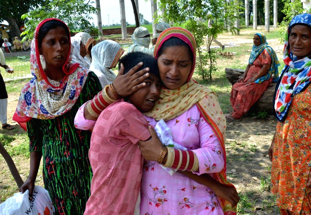 The grief stricken family members of Kirpal Singh who died after allegedly drinking spurious liquor, at Muchhal village about 30 kms from Amritsar on August 1, 2020. Even as the toll in the ... - Kirpal Singh and Balwinder Kaur