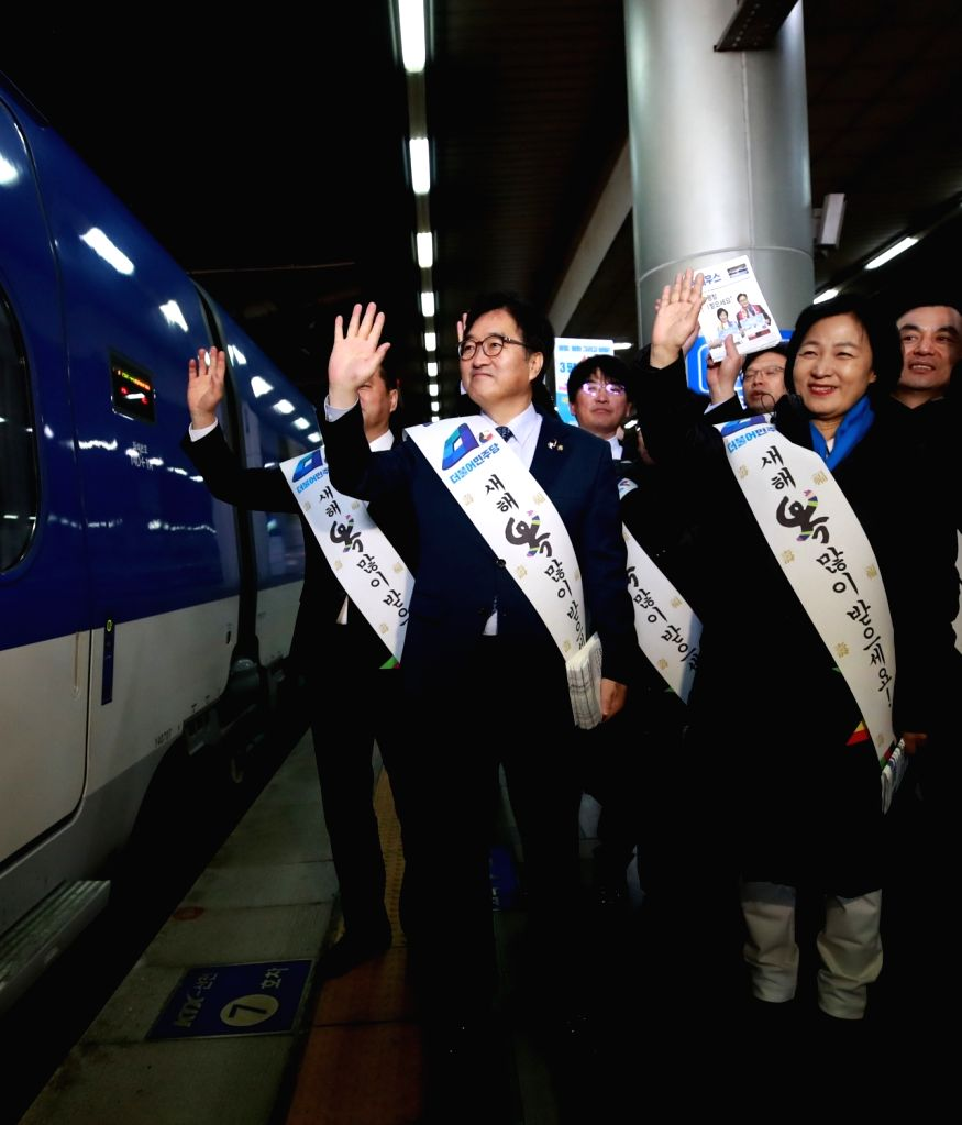 The leadership of the ruling Democratic Party, including its chief, Choo Mi-ae (R), sends off homebound passengers at Seoul Station on Feb. 14, 2018, as South Korea's annual exodus for Seol, ...