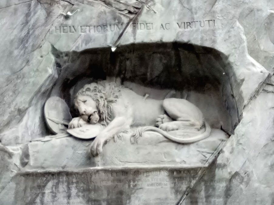 """The Lion Monument, one of Switzerland's most loved icons. It's a giant dying lion carved into the cliff face of a former sandstone quarry, above a pond and set in a landscaped garden in this medieval town. It is often referred to as the """"saddest ston"""