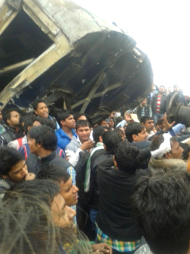 The mangled bogies of the EMU (electric multiple unit) shuttle train that collided head on with an express train near village Baghola in Palwal district of Haryana, about 80 km from New Delhi ...