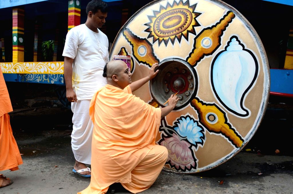 The members of ISCON society paint the wheels of a Lord Jagannath's chariot ahead of the Rath Yatra festival in Kolkata on July 2, 2016.