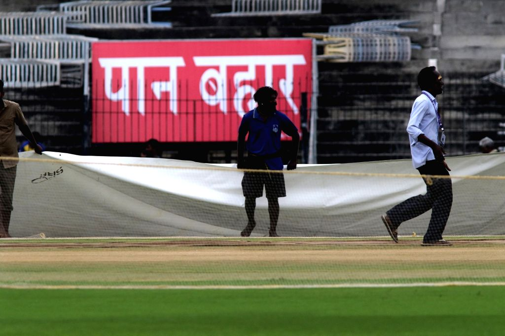 The pitch at MA Chidambaram stadium being covered with plastic sheets during rains ahead of the 1st one-day international (ODI) match between India and West Indies, in Chennai on Dec 13, ...
