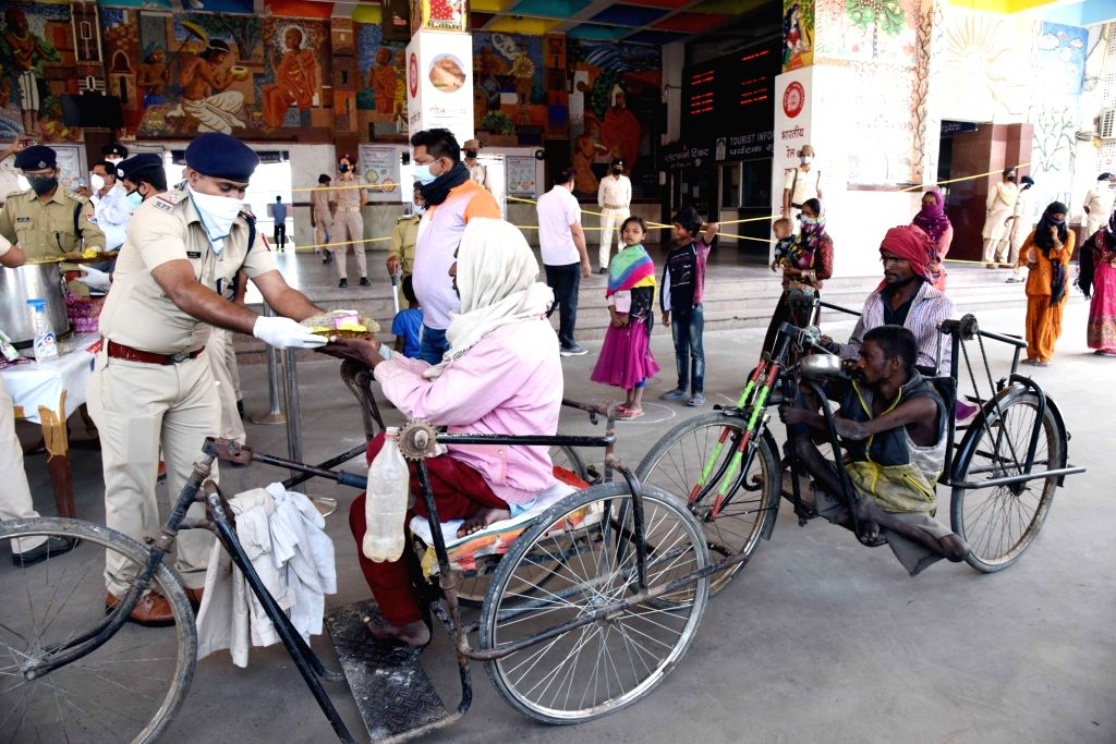The Railway Protection Force (RPF) personnel distribute food among the specially abled at the Patna Junction Railway Station on Day 5 of the 21-day countrywide lockdown imposed to contain the ...