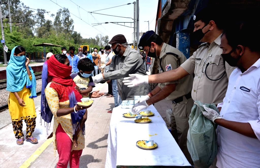 The Railway Protection Force (RPF) personnel distribute food among the poor people at Mandawali Chandra Vihar Junction on Day 7 of the 21-day nationwide lockdown imposed as a measure to ...