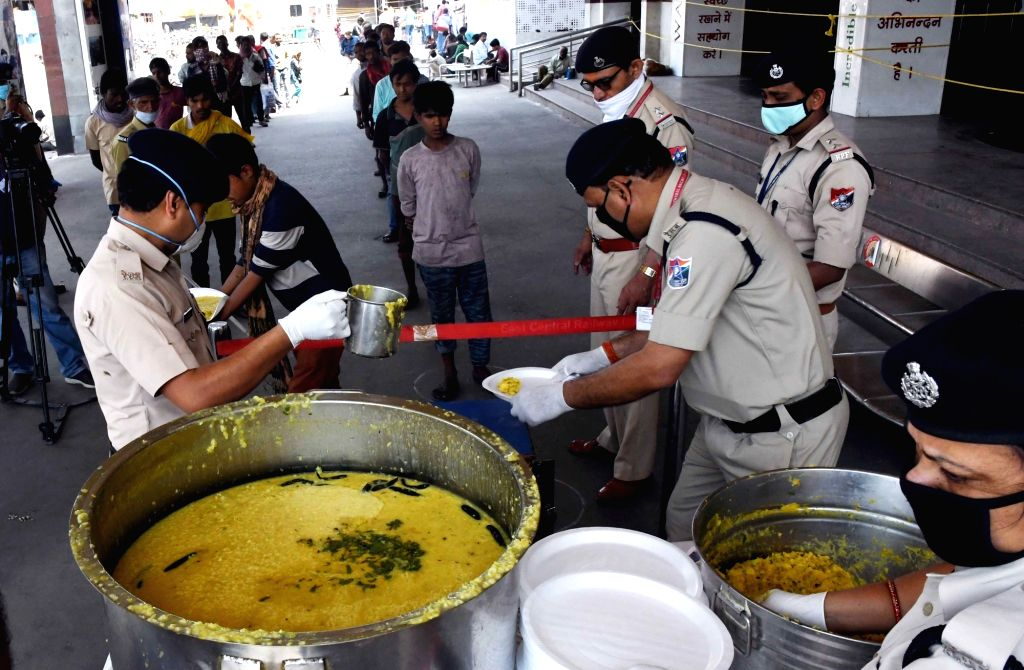 The Railway Protection Force (RPF) personnel serve food to the poor, needy and homeless people at the Patna Junction Railway Station during the 21-day nationwide lockdown imposed as a ...
