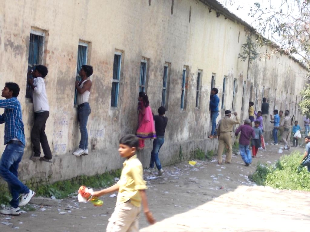 The relatives of  students appearing in board examinations help them cheat from outside the exam centre in Hajipur of Bihar on March 19, 2015.