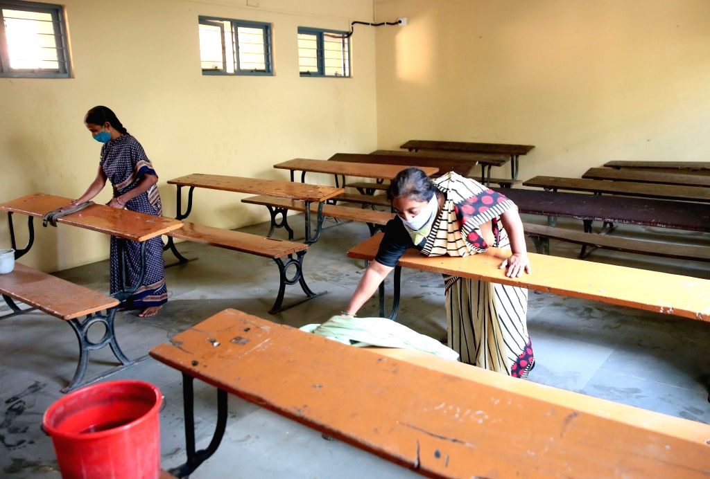 The sanitation staff of Basaveshwara College cleans desks with disinfectant as a precautionary measure against COVID-19 ahead of conducting the remaining Secondary School Leaving ...