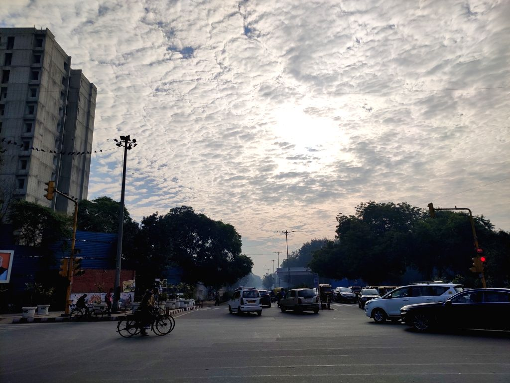 The sun peeps in from behind the clouds through the patchy skies on a chilly winter morning, in New Delhi on Jan 11, 2020.