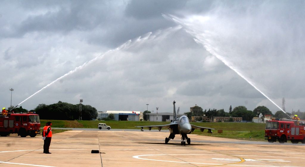 The Tejas Light Combat Aircraft (LCA) receives water cannon salute during its induction ceremony at HAL, in Bengaluru on July 1, 2016.