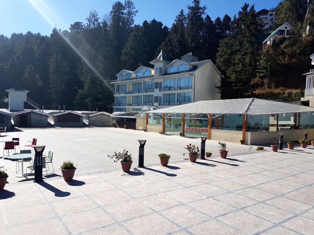 The terrace and swimming pool at the Royal Tulip Resort in Kufri-Himachal Pradesh with Cedar forest in the background.