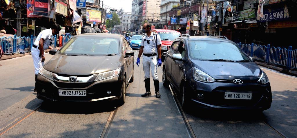 The Traffic Police personnel conduct checks on vehicles and intercept curfew violaters at Howrah Bridge during the 21-day nationwide lockdown imposed as a precautionary measure to contain ...