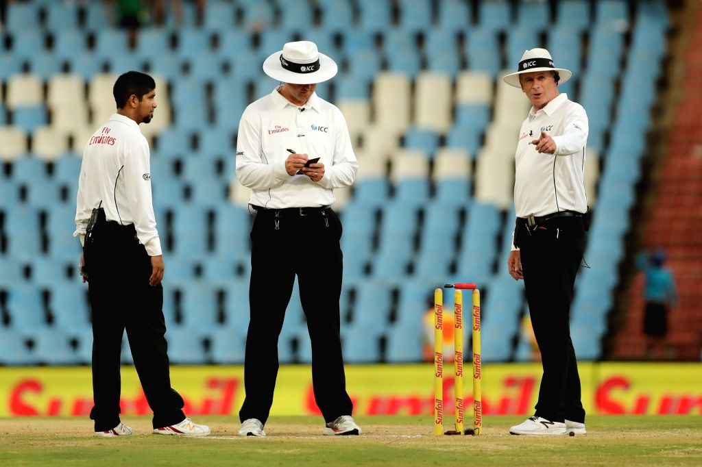 The umpires check the light by placing the light meter on the stumps for a reading during day 3 of the second Test match between South Africa and India at the Supersport Park Cricket ...