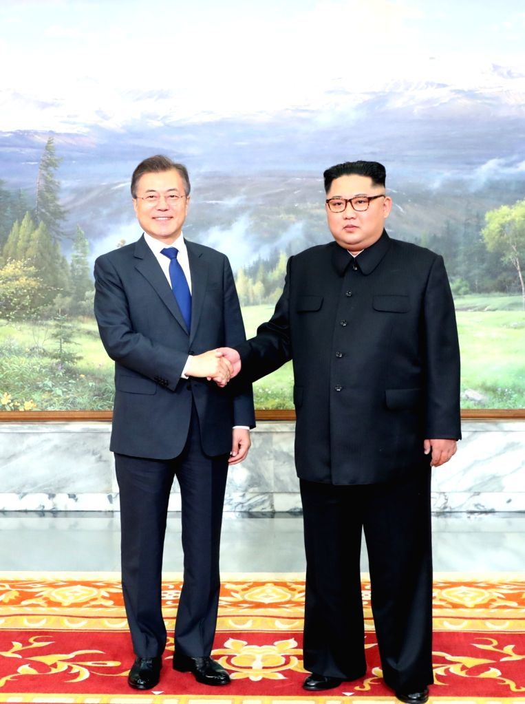 This photo released by Cheong Wa Dae shows South Korean President Moon Jae-in (L) shaking hands with North Korean leader Kim Jong-un ahead of their summit at Tongilgak on the northern side ...