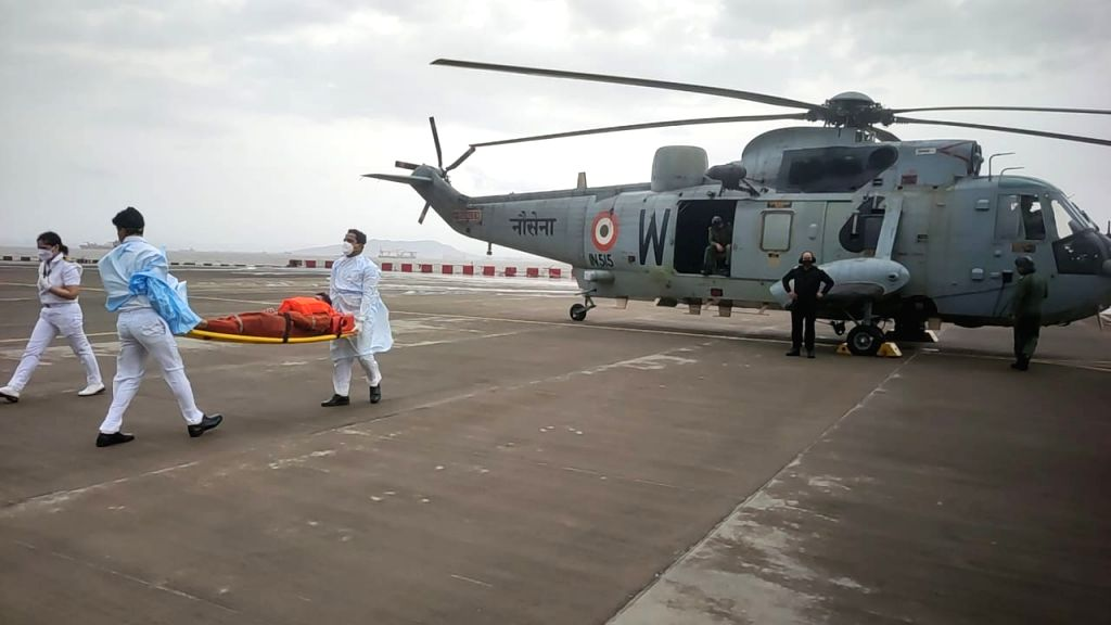 three personnel rescued by Seaking helicopter from Barge P305 being taken for medical attention at INS Shikra.