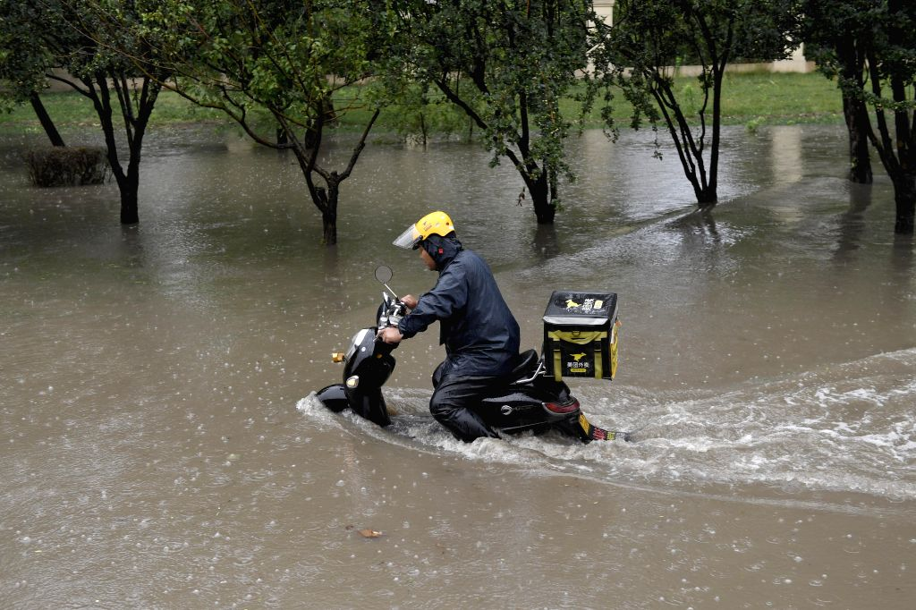 TIANJIN, Aug. 2, 2019 - A food delivery courier makes his way along a flooded road in Hedong District of Tianjin, north China, Aug. 2, 2019. Some roads in downtown Tianjin were flooded, due to the ...