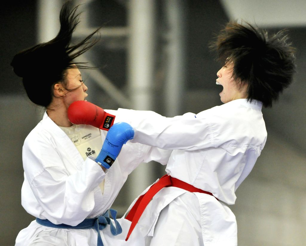 East Asia's Japanese player Miki Kobayashi (R) competes with Mid-Asia's Kazahstan player Zajharova Sabina in the women's 55kg+ contest of Karate during the women's group match at the 2nd ...