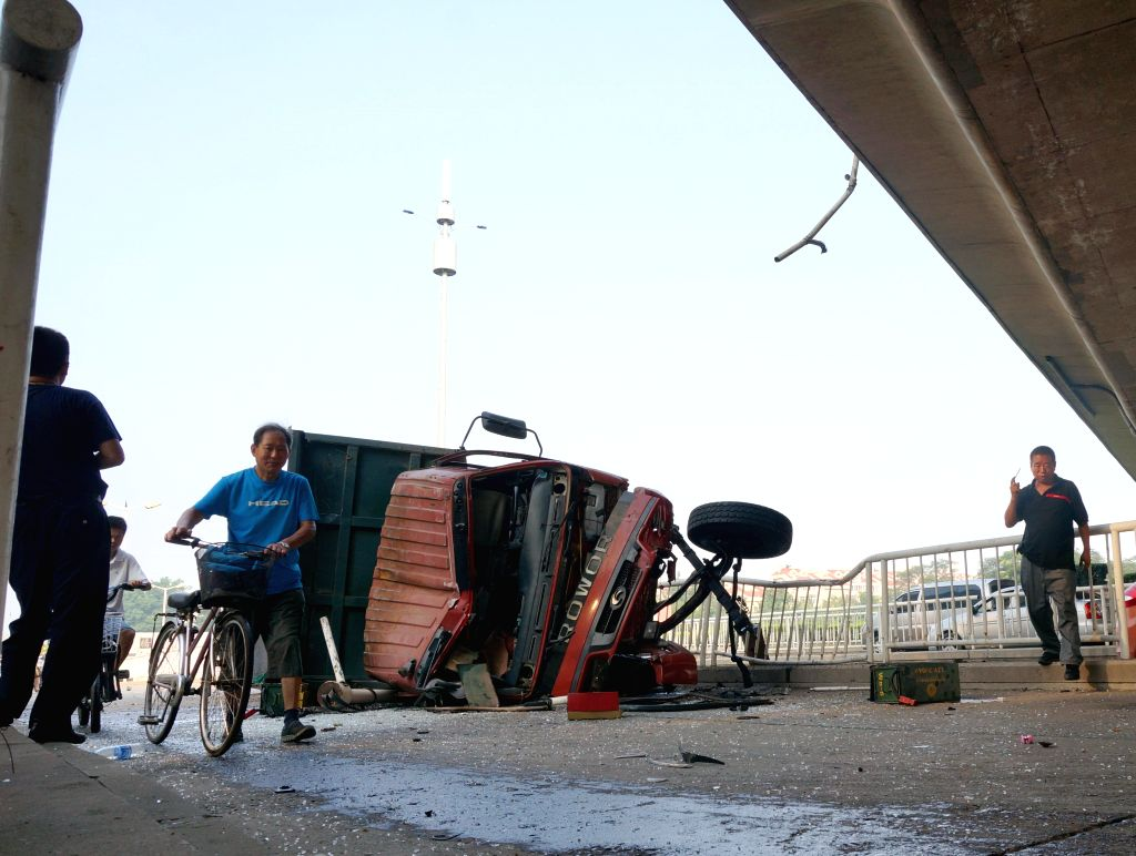 Photo taken on July 19, 2014 shows the scene of a road accident in which a truck falls from a bridge in Tianjin, north China. A truck ran into guardrails and fell ..