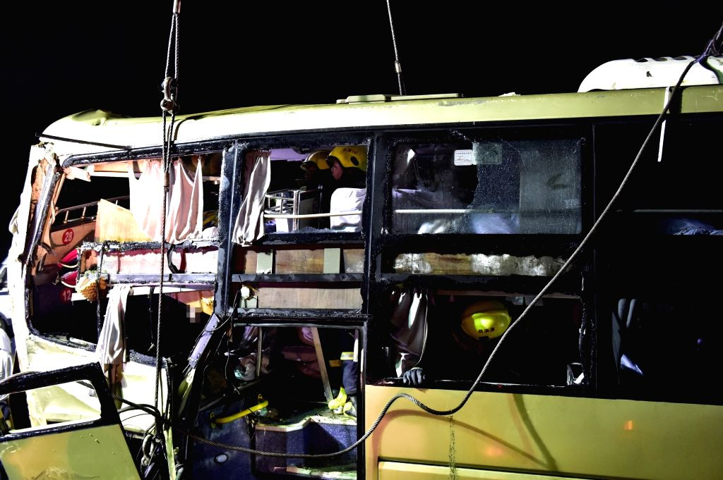TIANJIN, July 2, 2016 - Rescue workers clean up the accident bus in Baodi section of north China's Tianjin, on July 2, 2016. A bus carrying 30 people rushed out of an expressway Friday night in north ...