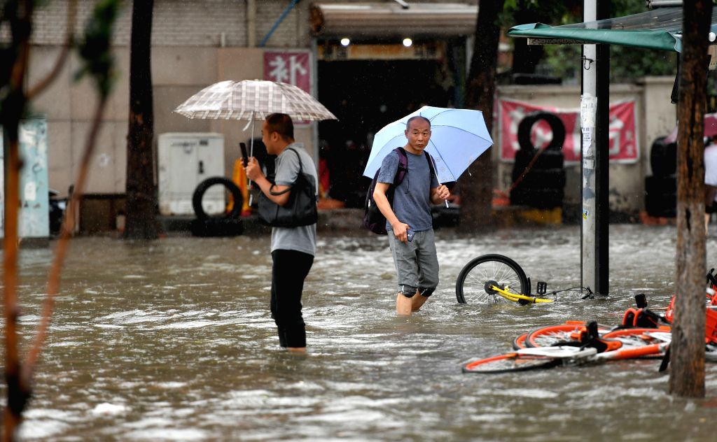 TIANJIN, July 24, 2018 - Pedestrians walk on a flooded road in Nankai District of north China's Tianjin Municipality, July 24, 2018. Heavy downpours brought by Typhoon Ampil pounded Beijing and ...