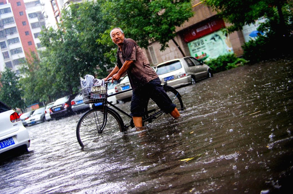 A man walks on a flooded street pulling his bike in north China's Tianjin, July 4, 2014. Heavy rainfalls hit the city on Friday.