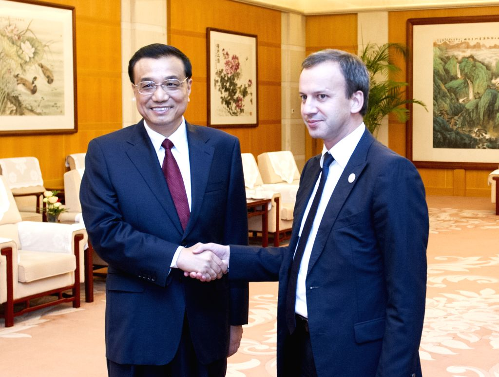 Chinese Premier Li Keqiang (L) meets with Russia's Deputy Prime Minister Arkady Dvorkovich on the sidelines of the Summer Davos in north China's Tianjin, Sept. ...