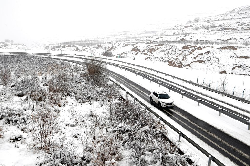 TIANSHUI, March 12, 2017 - A vehicle runs on snow-covered expressway in Dingxi City, northwest China's Gansu Province, March 12, 2017.