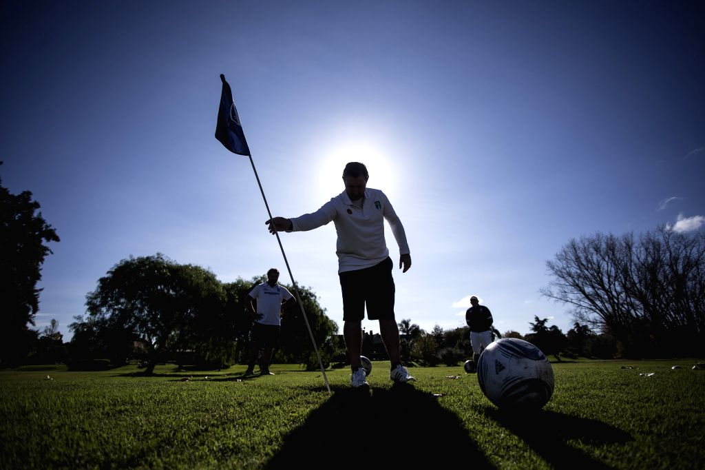 A FootGolf player adjusts a flag in a hole during a tournament in a golf field of Tigre, 35 kilometers away from Buenos Aires, capital of Argentina, on May 16, 2014. ..