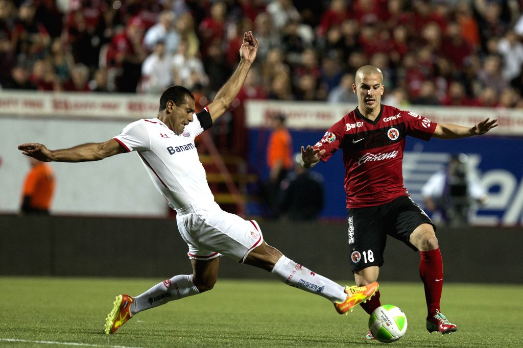 Xolos' Dario Benedetto (R) vies for the ball with Paulo Da Silva of Toluca during their quarterfinals match of the Liga MX, held in the Caliente Stadium, in the city .