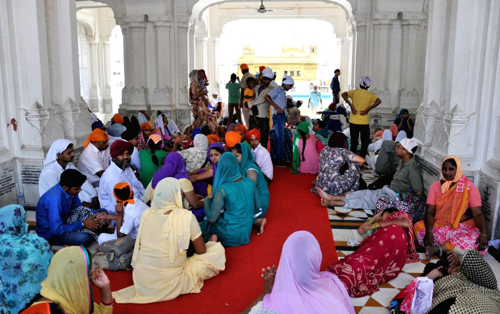 To protect themselves from the sweltering sun, devotees taking shelter in parikarma of Golden Temple in Amritsar on June 17, 2014.
