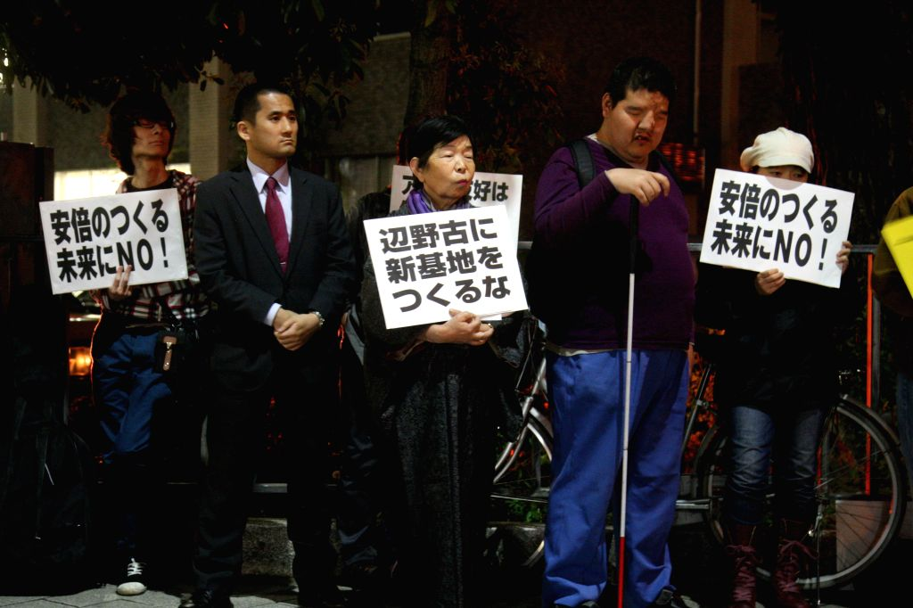 People hold slogans during a protest against Barack Obama's visit to Japan, in Tokyo, Japan, April 23, 2014. Obama arrived in Japan on a four-country trip through ...