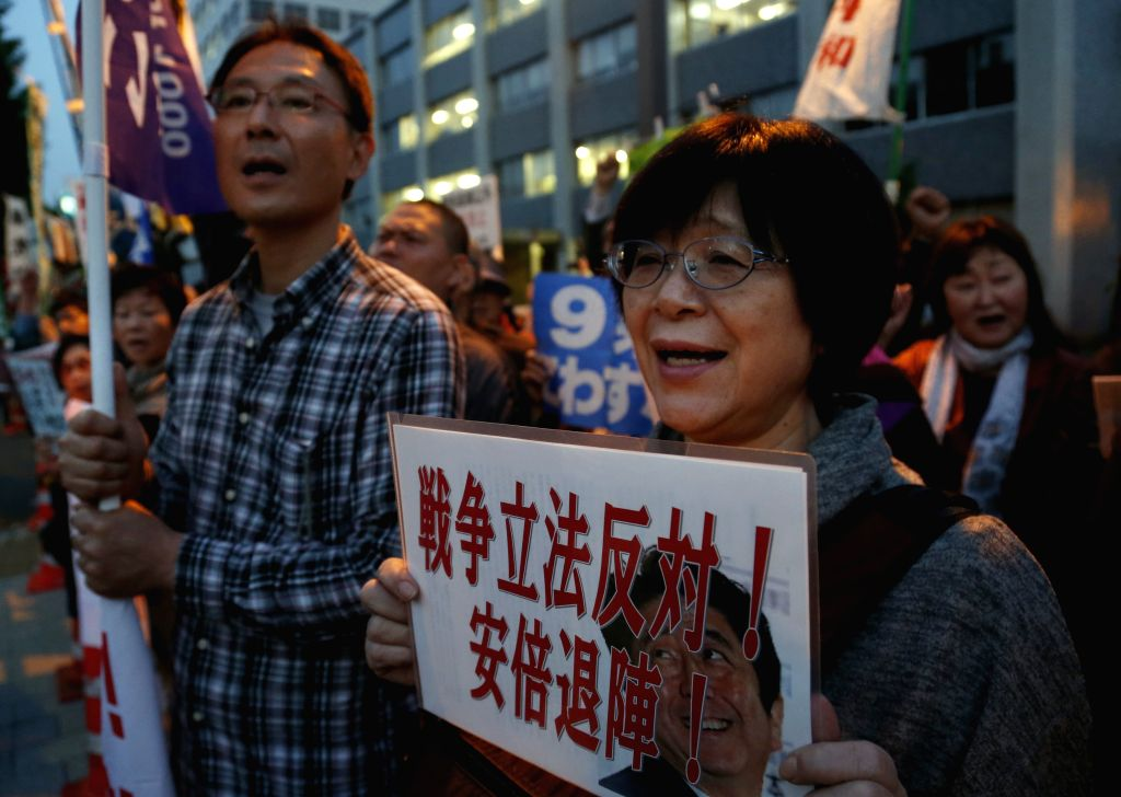People attend a protest against revising Japan-U.S. defense cooperation guidelines in front of the Prime Minister official residence in Tokyo, Japan, April 27, 2015. ...