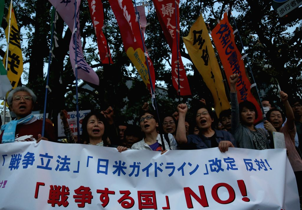 People holding a banner shout slogans during a protest against revising Japan-U.S. defense cooperation guidelines in front of the Prime Minister official residence ...