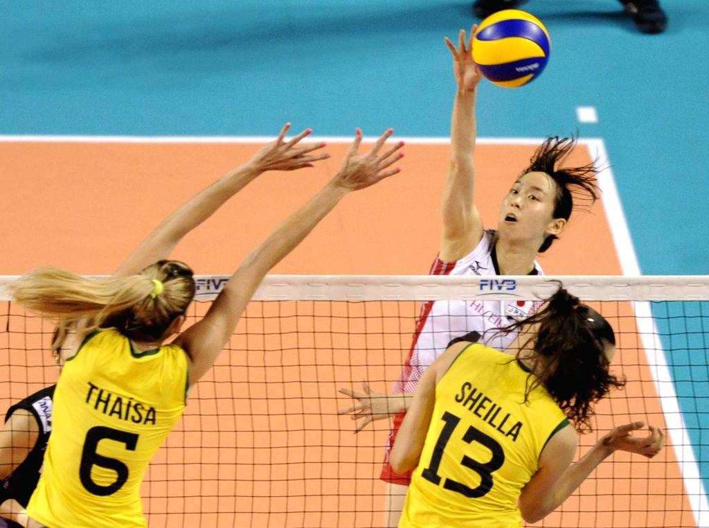 Arisa Takada (C) of Japan spikes the ball against Brazil during the final round match of FIVB Women's Volleyball World Grand Prix 2014 in Tokyo, Japan, Aug. 24, 2014.
