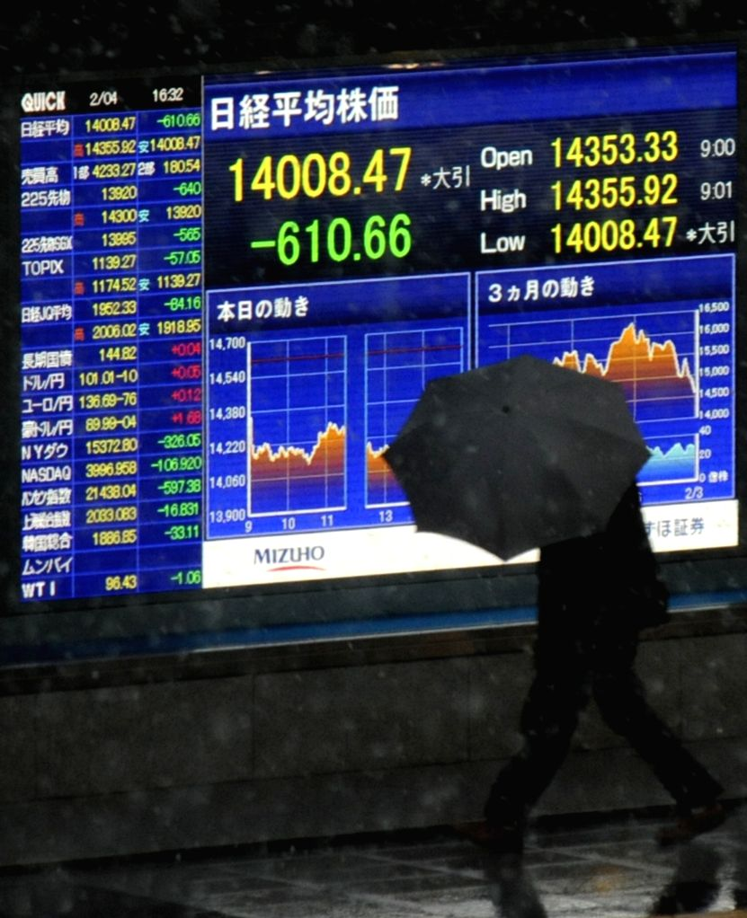 TOKYO, Feb. 4, 2014 (Xinhua) -- A man walks past an electronic board showing the stock index in Tokyo, Japan, Feb. 4, 2014. Tokyo stocks tumbled on Tuesday, with the Nikkei index ending 4.18 percent lower, hitting the lowest closing level since last