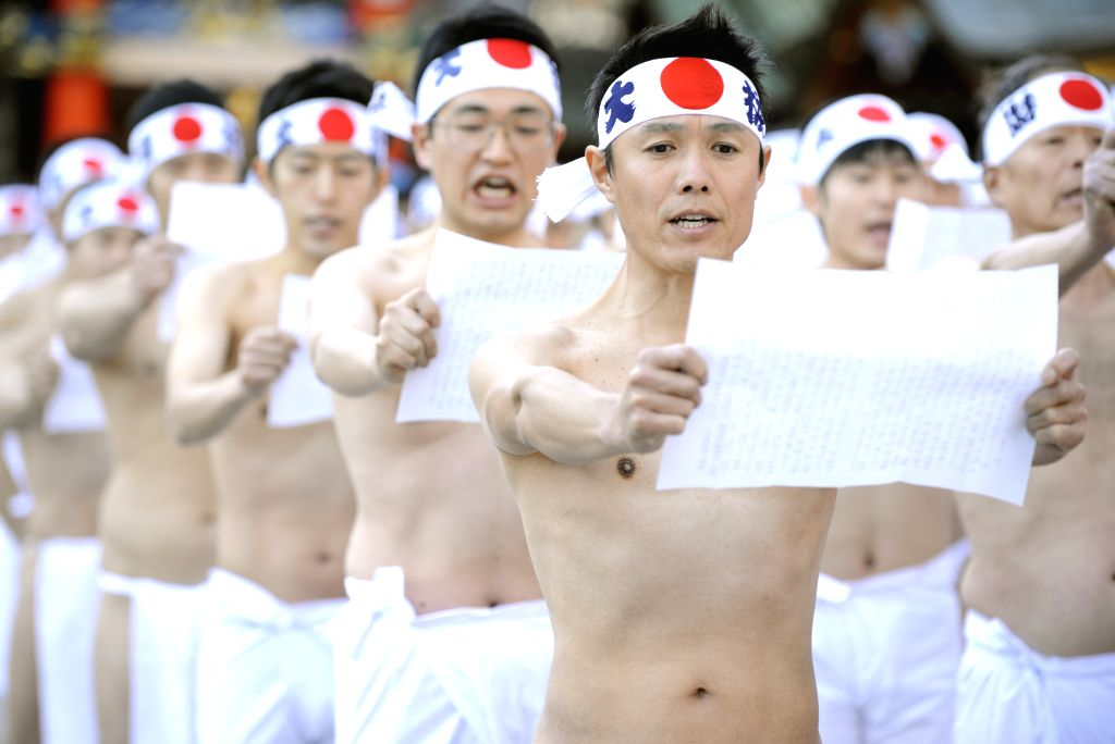 Believers in Shinoism read ancient Japanese Liturgy prior to an annual cold-endurance festival at the Kanda Myojin Shinto Shrine in Tokyo, Japan, Jan. 10, 2015. Some .