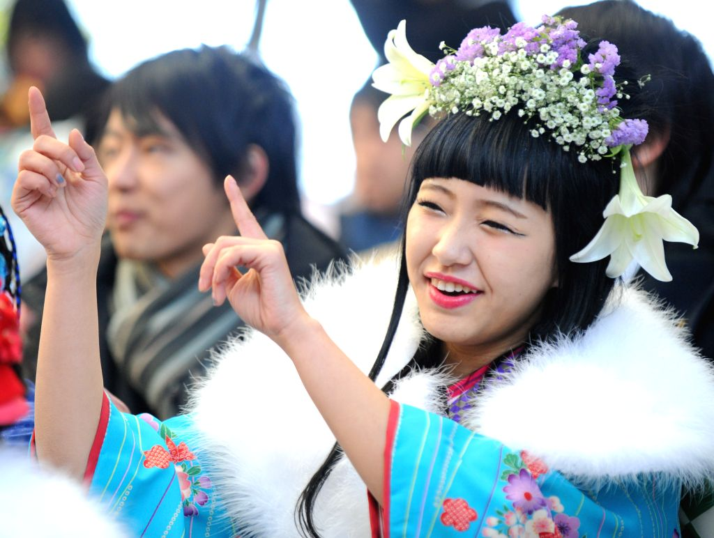 A young girl dressed in traditional kimono dances during the Coming-of-Age Day ceremony at the Tokyo Disneyland in Urayasu, suburban Tokyo, Japan, Jan. 12, 2015. ...