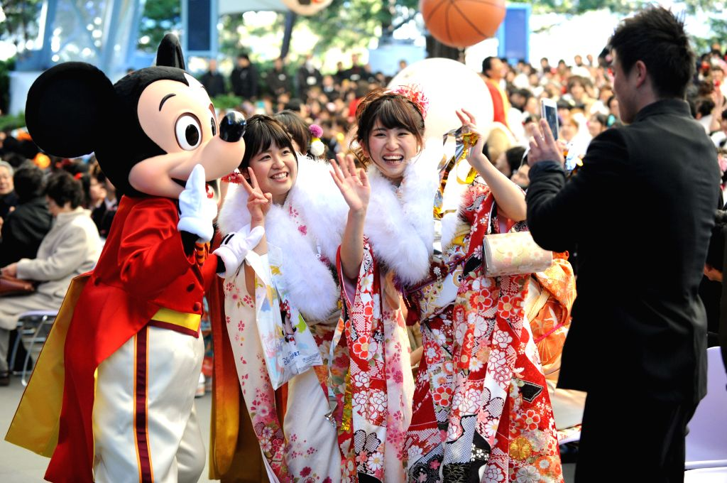 Young girls dressed in traditional kimonos take photos with the Mickey Mouse during the Coming-of-Age Day ceremony at the Tokyo Disneyland in Urayasu, suburban Tokyo,