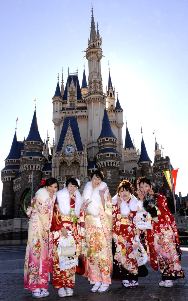 Young girls dressed in traditional kimonos pose for photos during the annual Coming-of-Age Day ceremony at the Tokyo Disneyland in Urayasu, suburban Tokyo, Japan, ...
