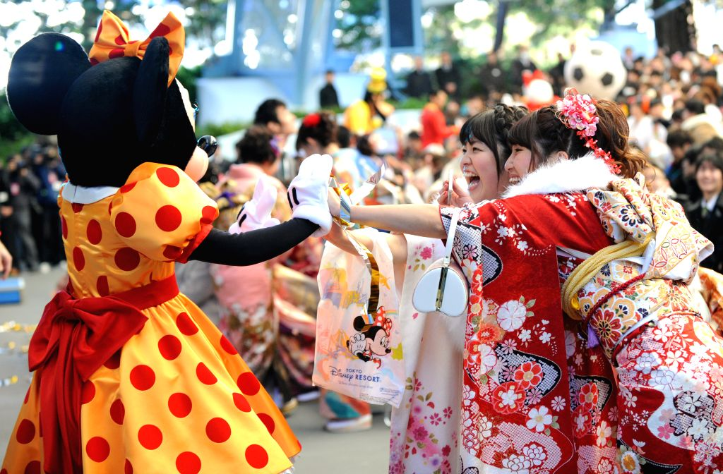 Young girls dressed in traditional kimonos attend the annual Coming-of-Age Day ceremony at the Tokyo Disneyland in Urayasu, suburban Tokyo, Japan, Jan. 12, 2015. ...